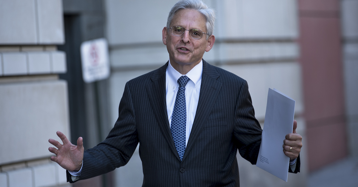 Merrick Garland holds a piece of paper while standing