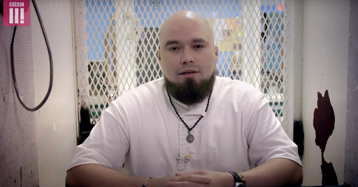 John Henry Ramirez pictured sitting in the visitation room in prison, behind Plexiglas