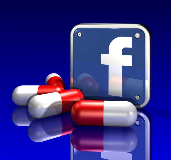 3d illustration of a large blue Facebook logo standing upright behind three large red and white pills on a blue reflective surface