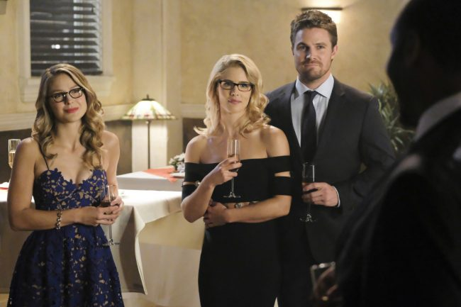 """image: Bettina Strauss/The CW Supergirl -- """"Crisis on Earth-X, Part 1"""" -- Pictured (L-R): Melissa Benoist as Kara, Emily Bett Rickards as Felicity Smoak and Stephen Amell as Oliver Queen -© 2017 The CW Network, LLC. All Rights Reserved"""