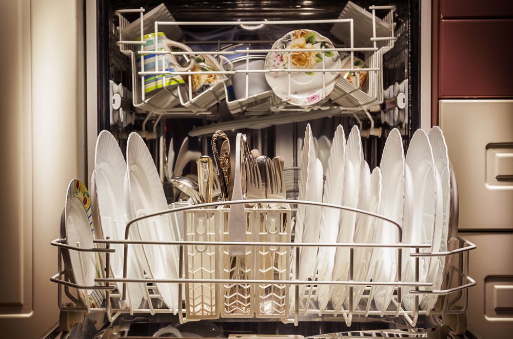 Shutterstock image of dirty dishes in a dishwasher, representing domestic labor