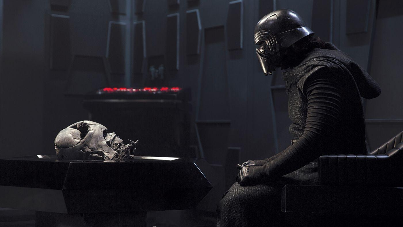 Adam Driver as Kylo Ren looking at Darth Vader's helmet in Star Wars: The Force Awakens