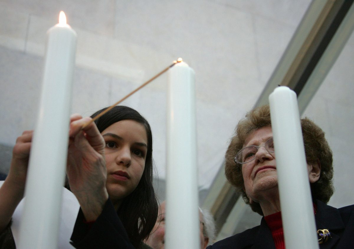"Paris, FRANCE: A woman lights a candle, 24 April 2006, at the holocaust memorial in Paris, as they attend a ceremony to commemorate the 76.000 Jewish victims sent from France to concentrations camp between 1942 and 1944, as part of the ""Yom HaShoah"", a day marking the annual Holocaust remembrance."