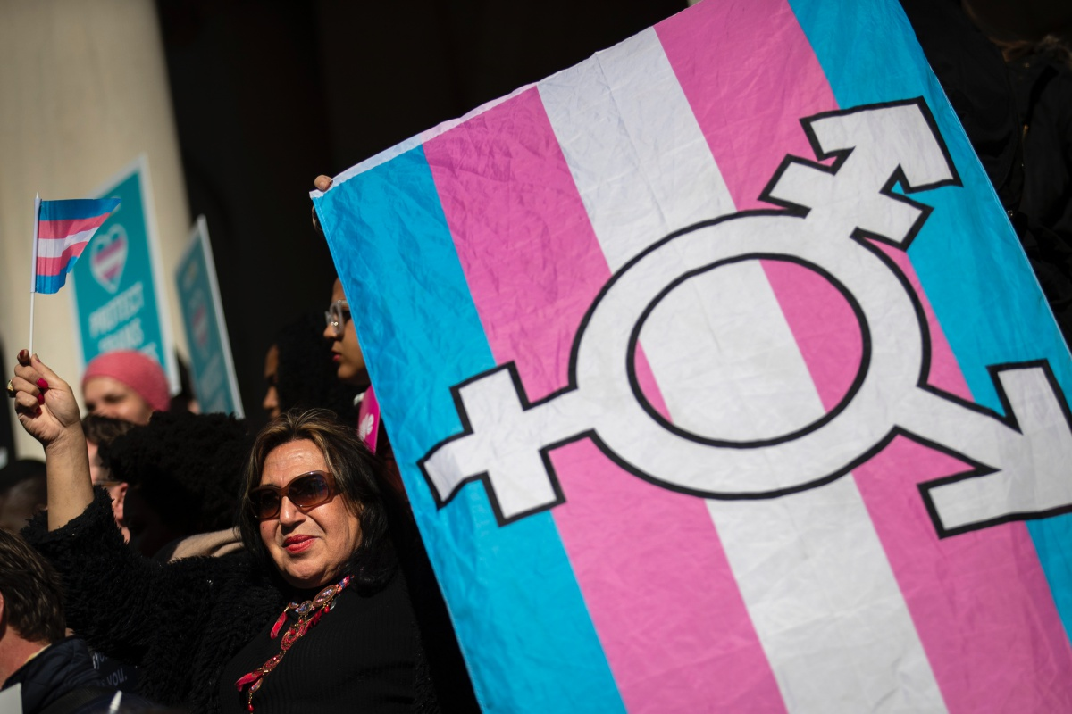 Protestor carries a transgender flag.