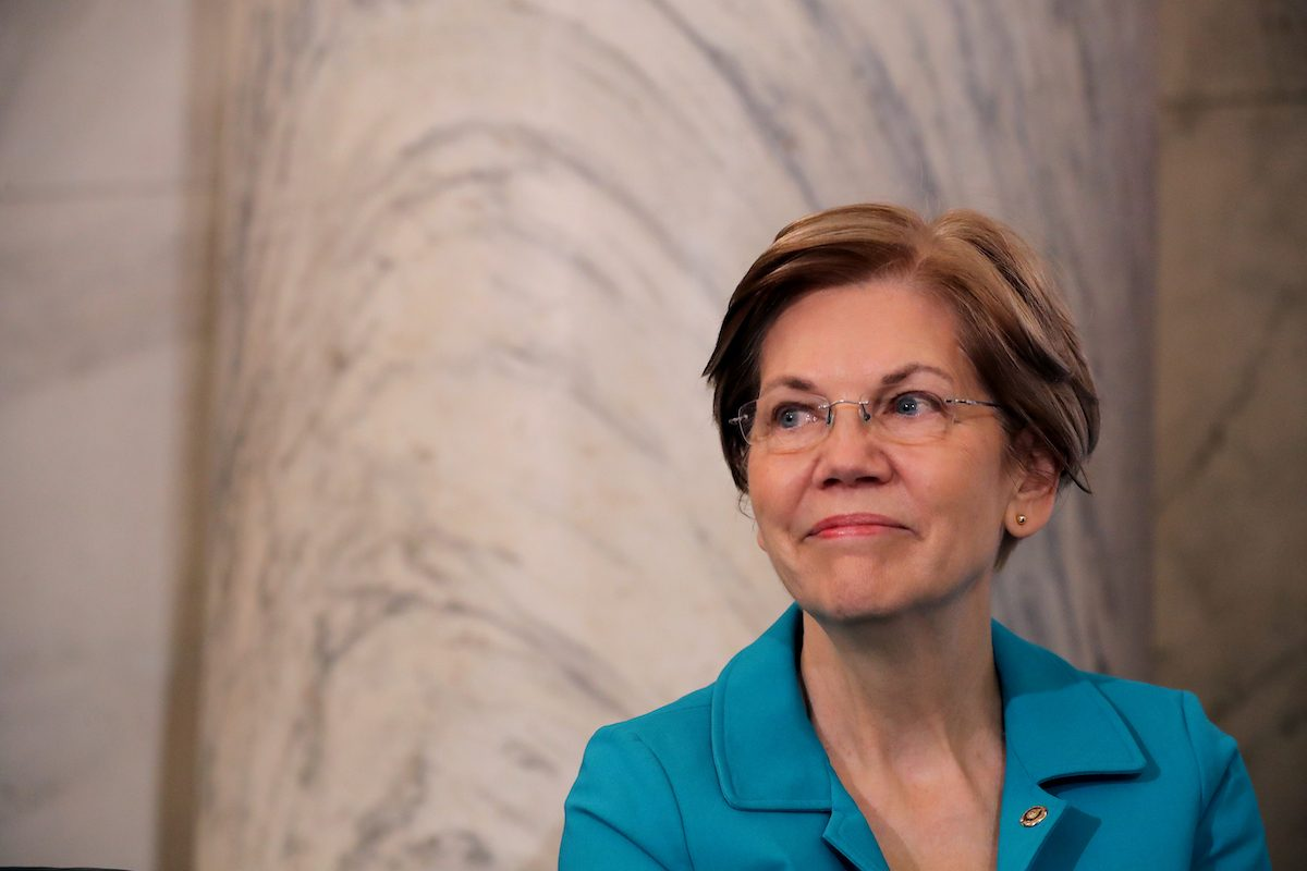 Elizabeth Warren stands against a marble wall looking charming and presidential.