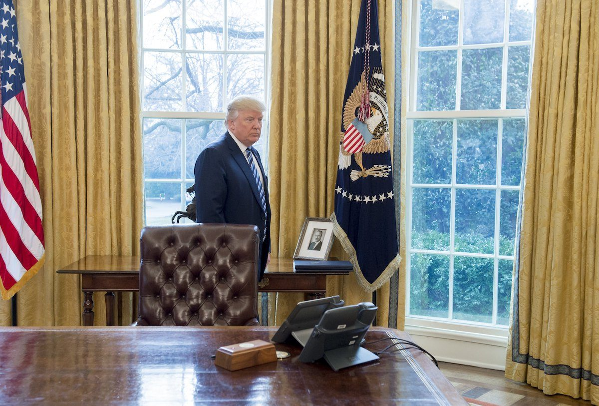 Donald Trump looks very small standing behind his desk in the Oval Office.