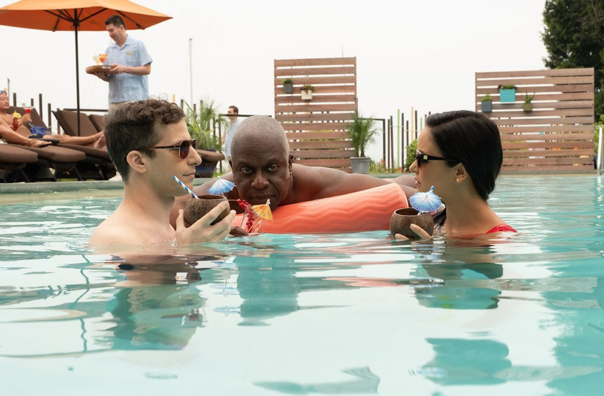 "BROOKLYN NINE-NINE -- ""Honeymoon"" Episode 601 -- Pictured: (l-r) Andy Samberg as Jake Peralta, Andre Braugher as Ray Holt, Melissa Fumero as Amy Santiago, drinking tropical cocktails from coconuts in a swimming pool"