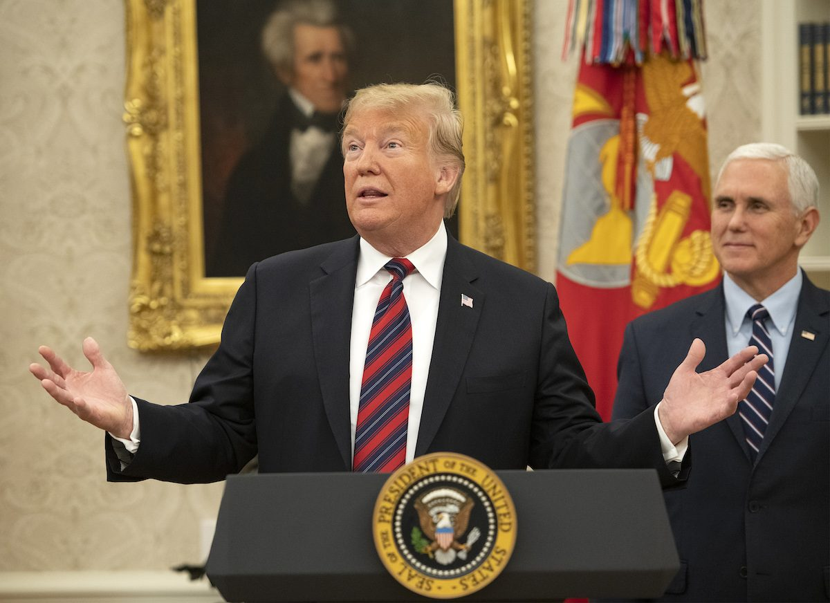 Donald Trump stands at a podium in the Oval Office with Mike Pence behind him.
