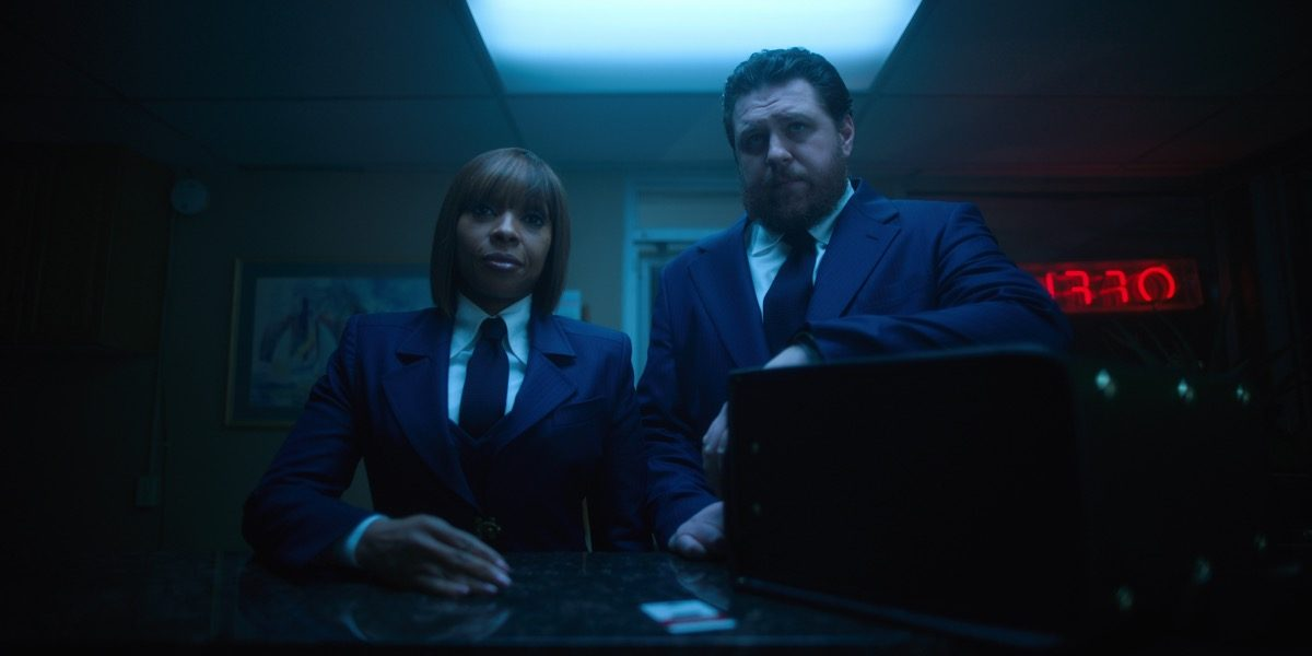 Mary J. Blige and Cameron Britton standing together wearing suits.