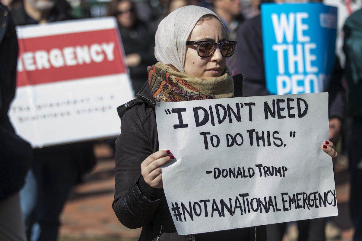 "Protestor holds a sign reading ""'I didn't need to do this.' -Donald Trump #NotaNationalEmergency"" during an ACLU demonstration"