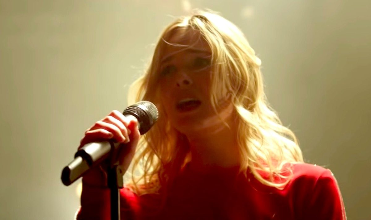 Elle Fanning singing into a microphone in Teen Spirit movie.