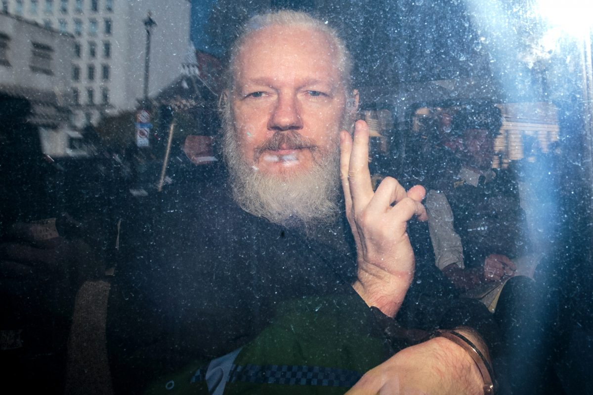 Julian Assange throwing up a peace sign after he was arrested