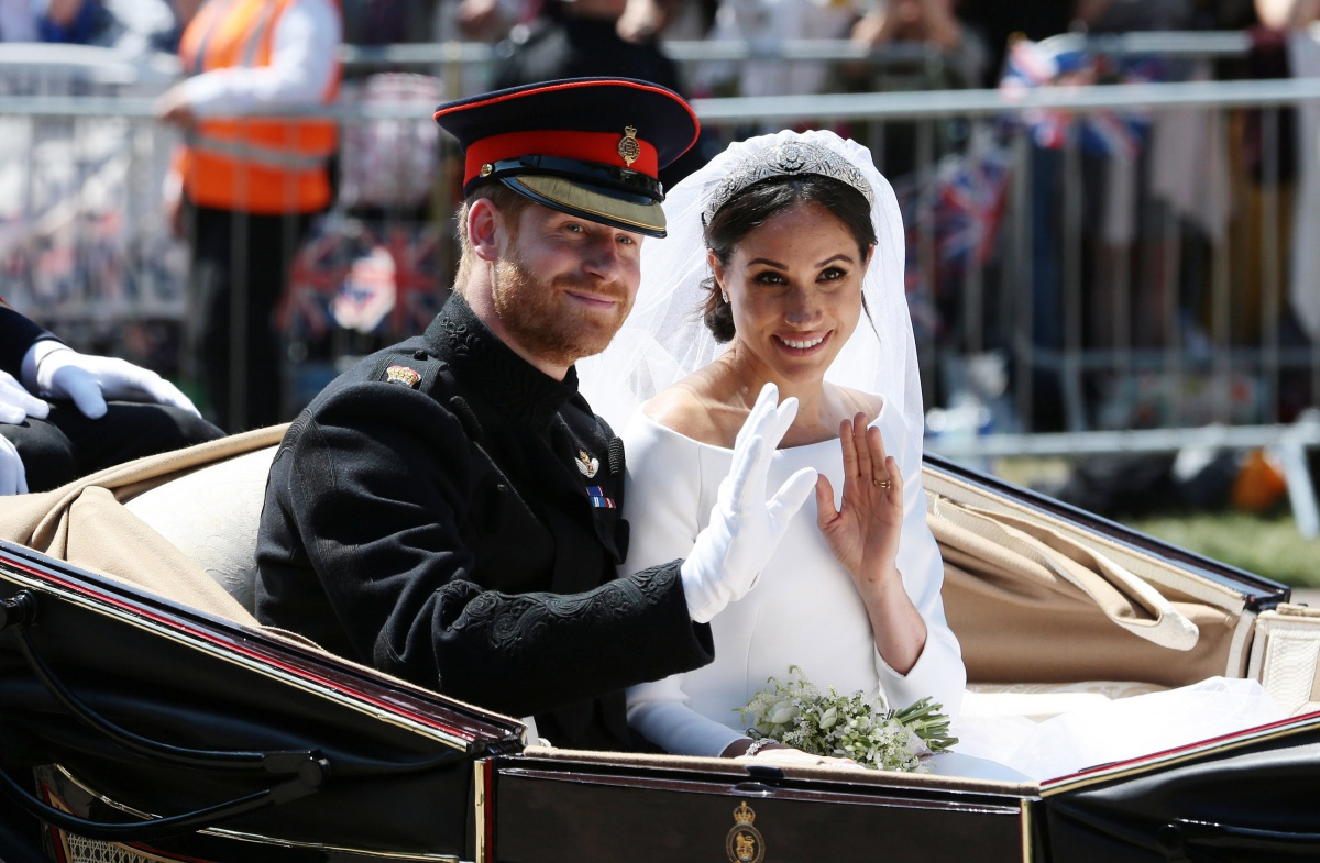 Prince Harry, Duke of Sussex and Meghan, Duchess of Sussex wave from the Ascot Landau Carriage during their carriage procession on Castle Hill outside Windsor Castle in Windsor, on May 19, 2018 after their wedding ceremony. (Photo by Aaron Chown - WPA Pool/Getty Images)