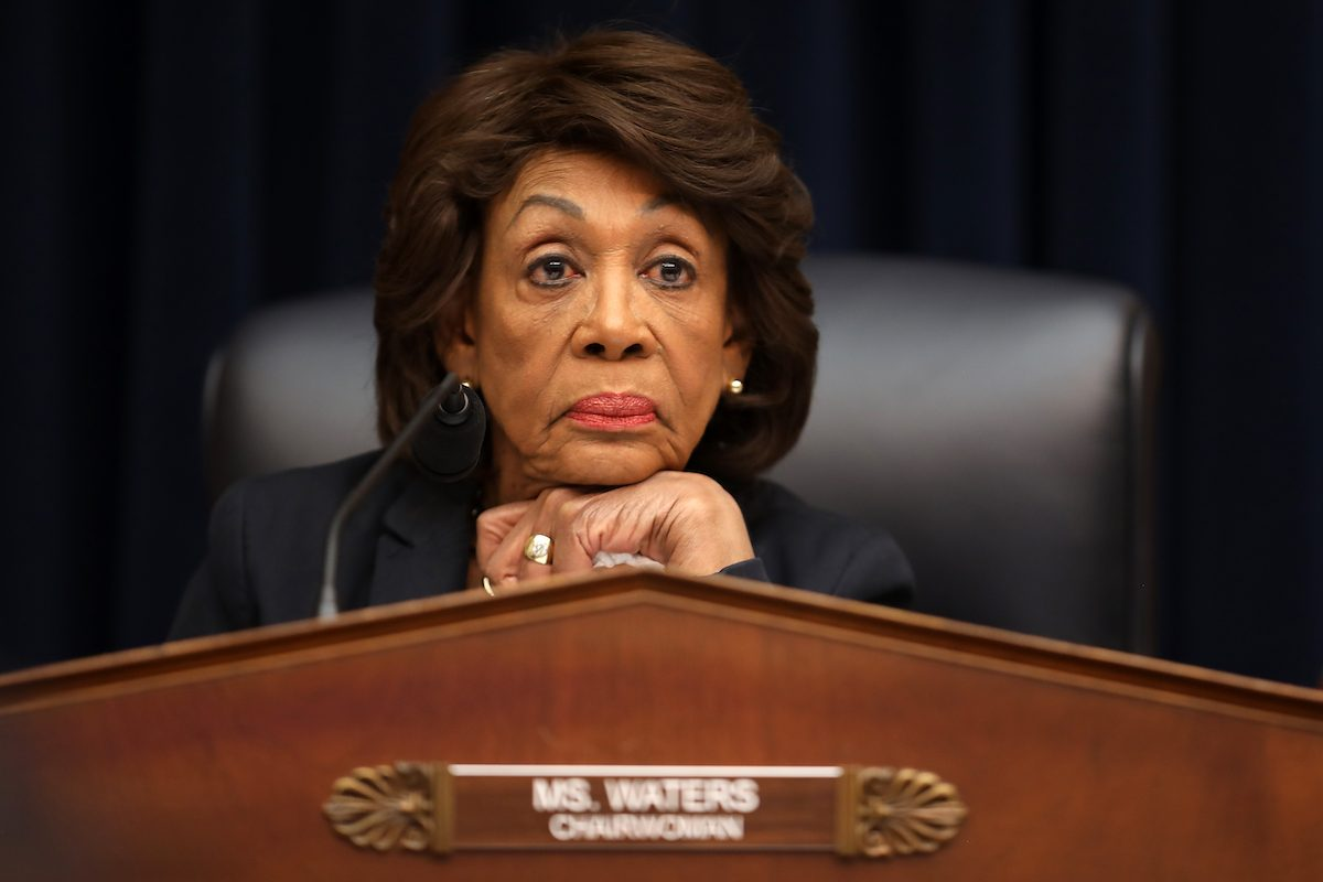 Congresswoman Maxine Waters rests her head on her chin, fresh out of patience, above a plaque reading Chairwoman.