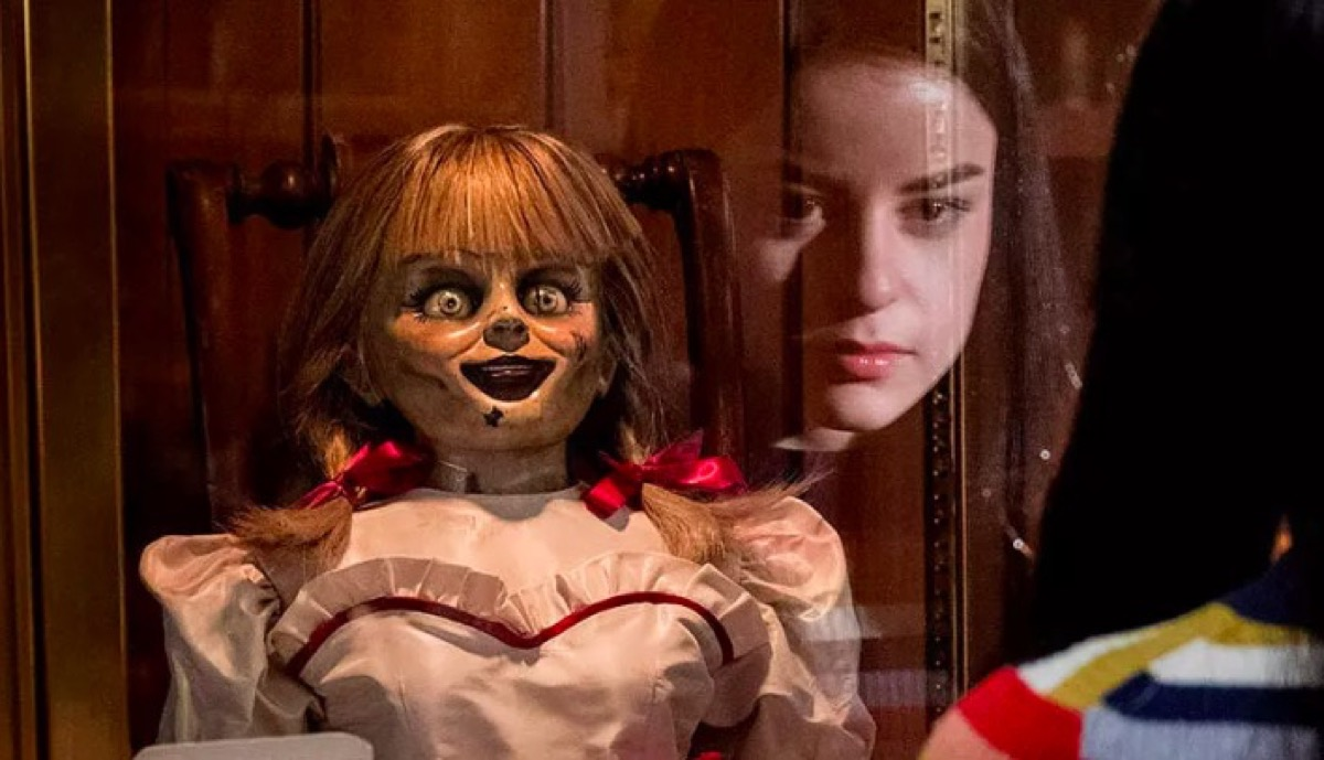 Spooky Annabelle doll being stared at by a child.