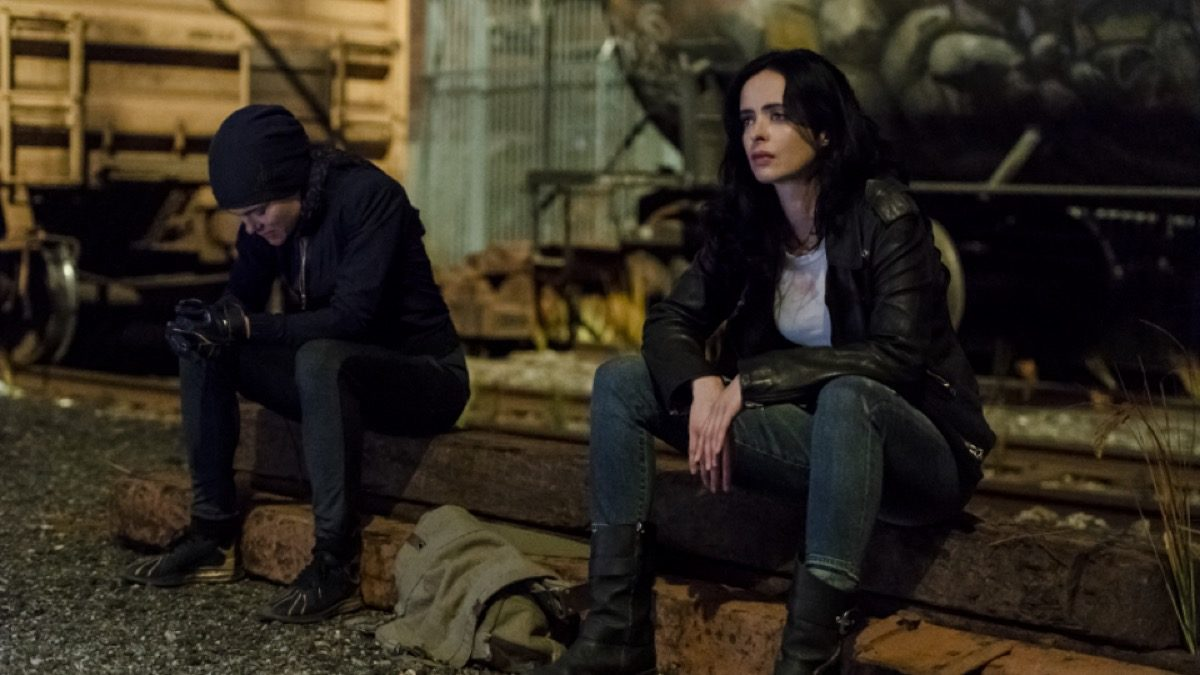 Trish and Jessica sit, looking unhappy and not looking at each other, in Marvel and Netflix's Jessica Jones season 3.