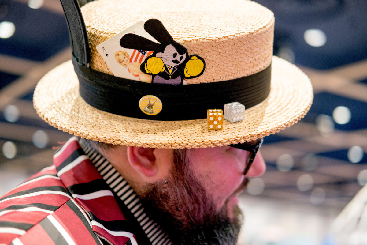 A man wears an old-fashioned straw hat with Disney details for Dapper Day.