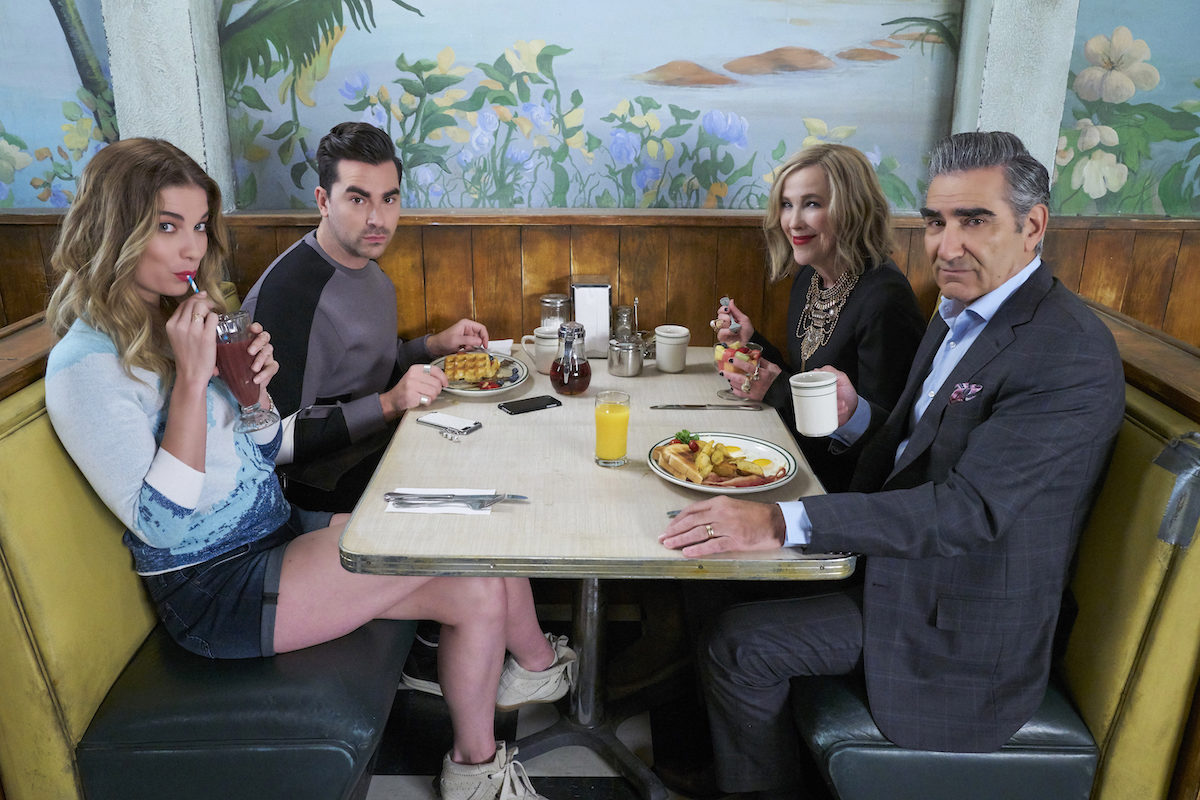 The cast of Schitt's Creek sits around a booth in the diner from the show.