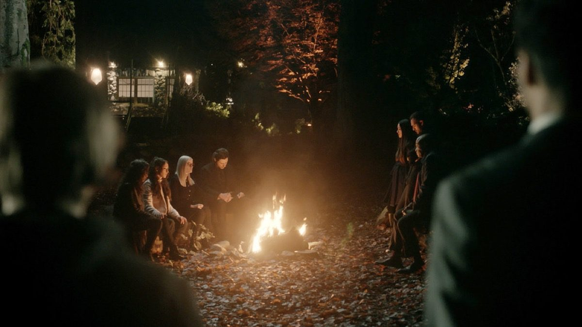 The Magicians characters sit around a campfire together.