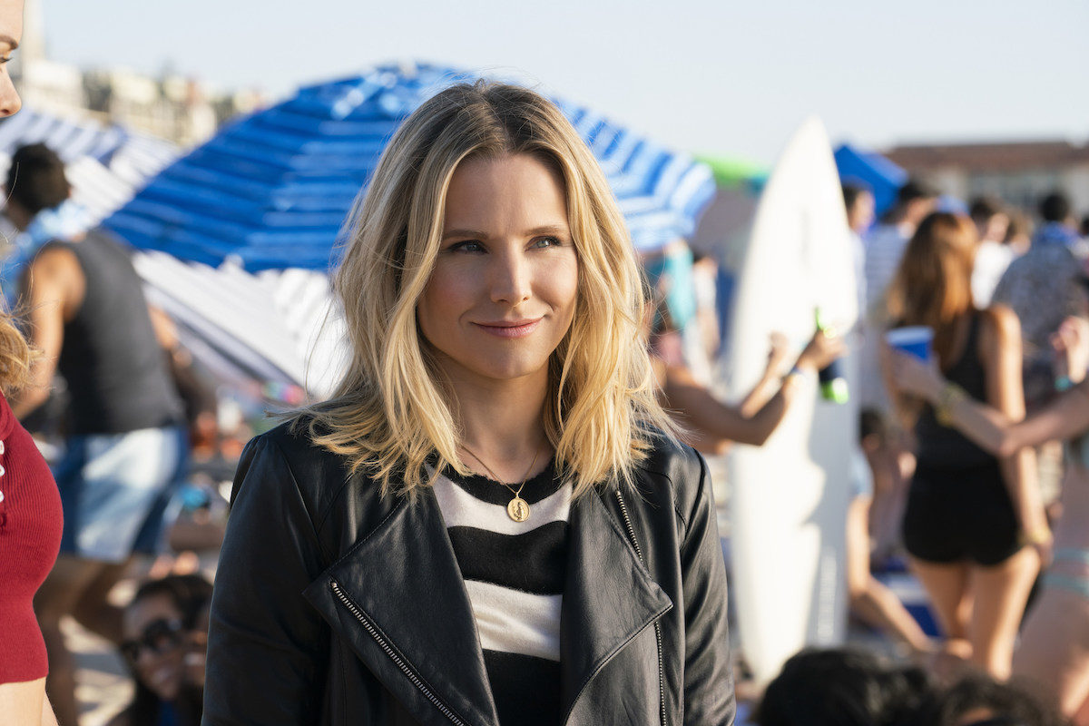 Veronica Mars (Kristen Bell) stands on a crowded beach in a leather jacket.