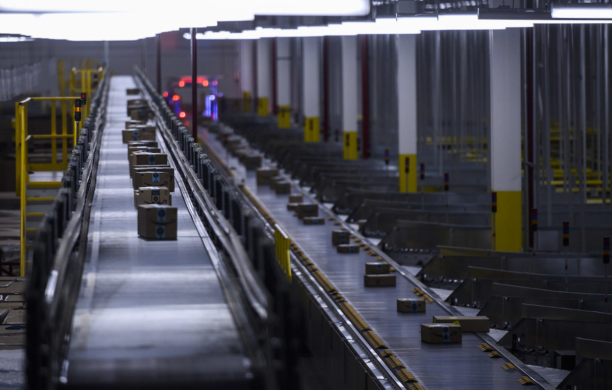 Amazon packages on a conveyor belt in a factory room.