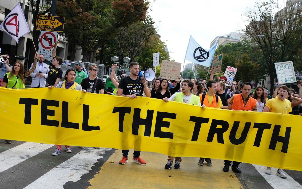Climate protesters carry a large banner reading 'TELL THE TRUTH.'