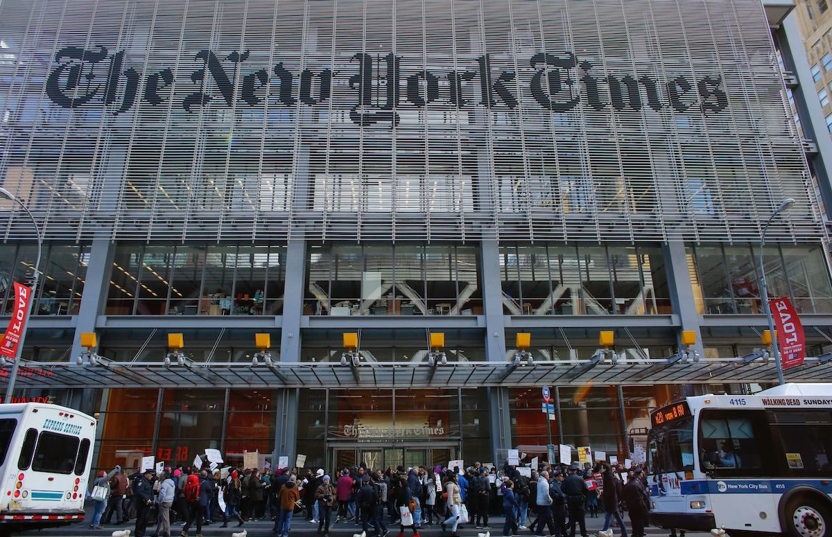 People take part in a protest outside the New York Times