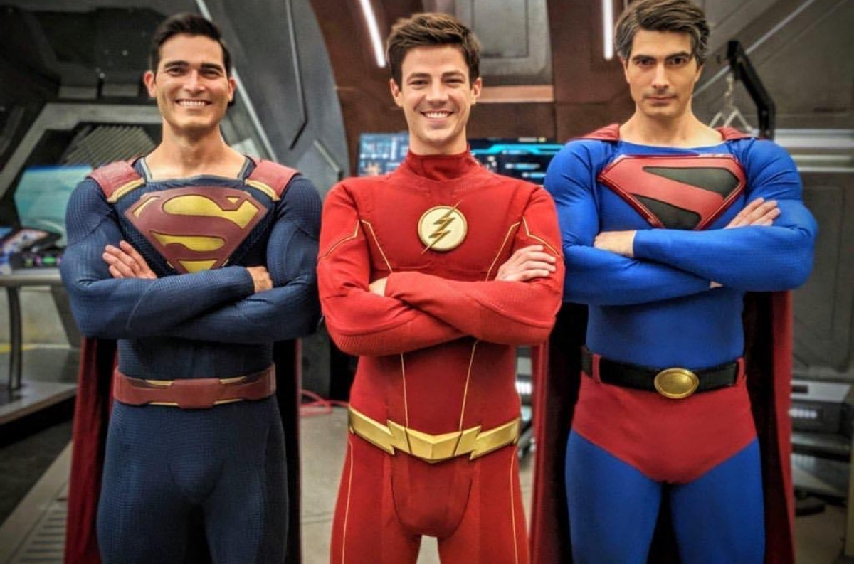 Grant Gustin's The Flash centered between Tyler Hoechlin and Brandon Routh, with both actors dressed in their Superman costumes.