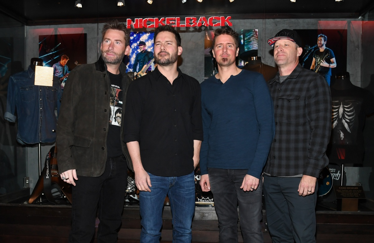 """Nickelback Memorabilia Case Dedication At The Hard Rock LAS VEGAS, NV - FEBRUARY 22: (L-R) Frontman Chad Kroeger, guitarist Ryan Peake, drummer Daniel Adair and bassist Mike Kroeger of Nickelback attend a memorabilia case dedication ahead of the band's five-night """"Feed the Machine"""" residency at The Joint inside the Hard Rock Hotel & Casino on February 22, 2018 in Las Vegas, Nevada. (Photo by Ethan Miller/Getty Images)"""
