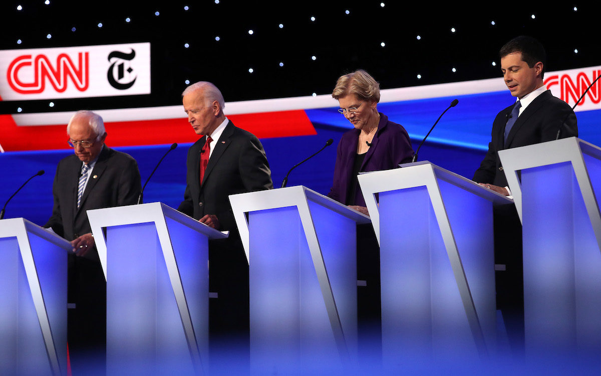 Bernie Sanders, Joe Biden, Elizabeth Warren, and Pete Buttigieg stand at their podiums on the stage of the fourth Democratic debate.