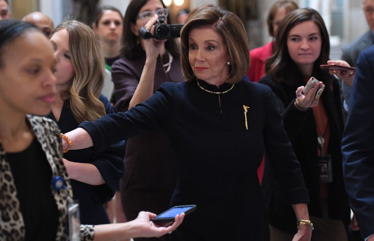 Nancy Pelosi, surrounded by reporters, walks to the House floor at the US Capitol.