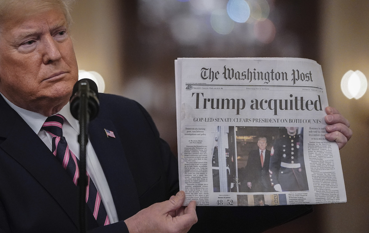 Donald Trump holds a copy of The Washington Post as he speaks in the East Room of the White House one day after the U.S. Senate acquitted on two articles of impeachment