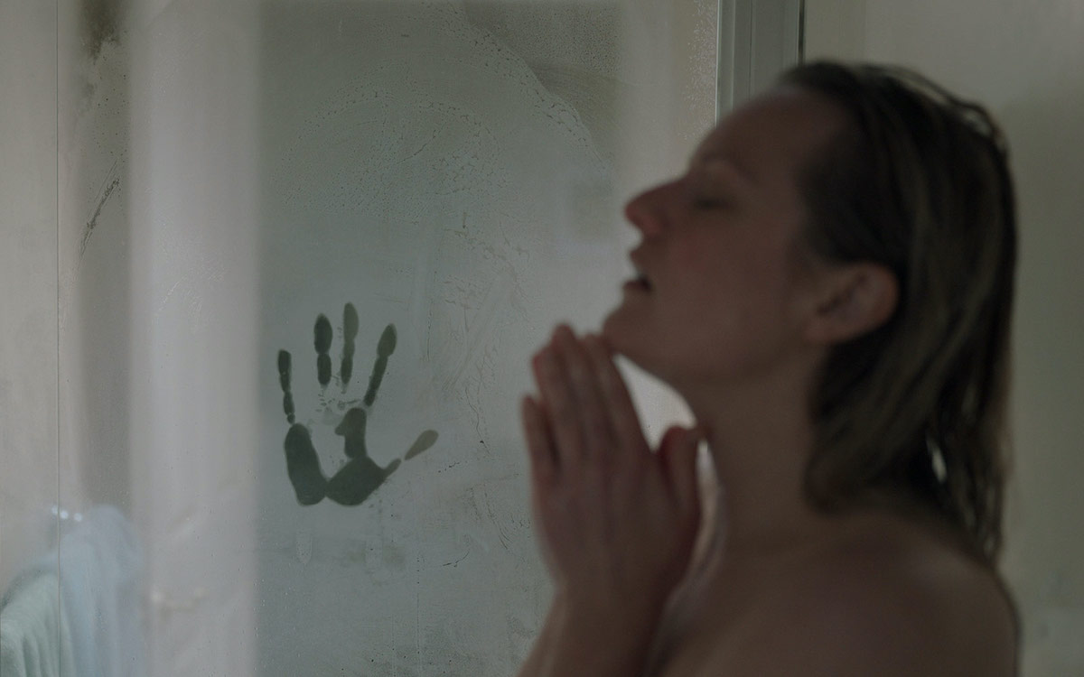 Elizabeth Moss takes a shower with a handprint in the steam.