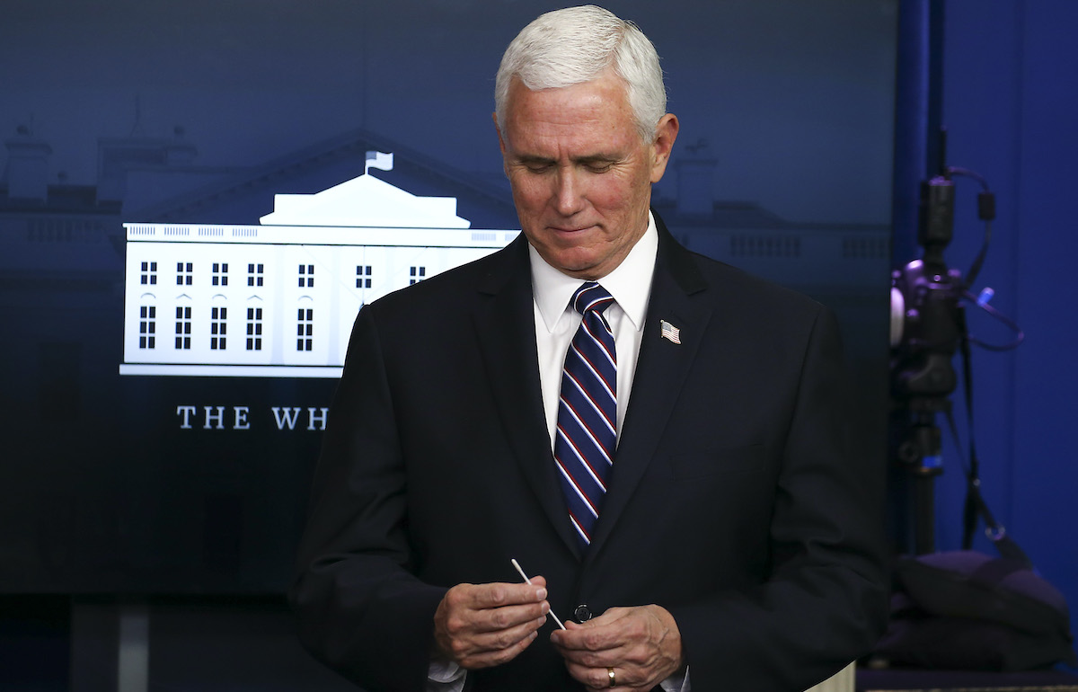 Mike Pence holds up a swab at the daily coronavirus briefing at the White House