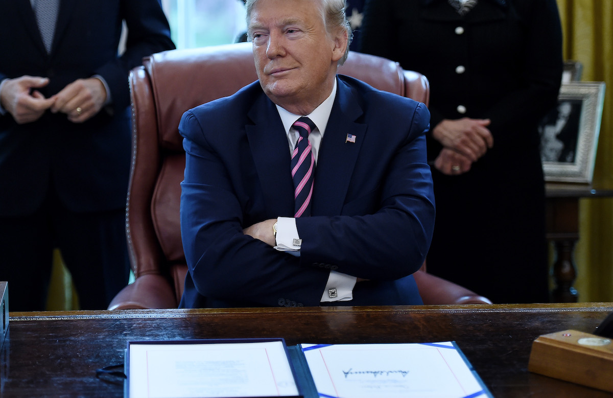 Donald Trump folds his arms and looks smug sitting behind the Oval Office desk.