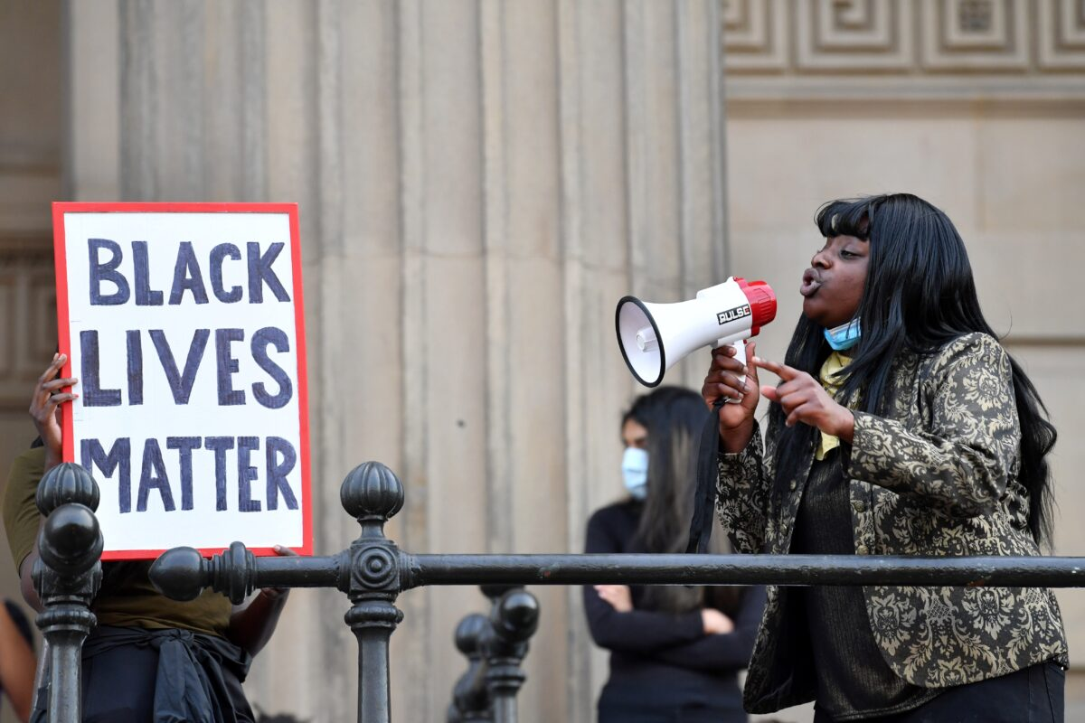 A protester addresses others through a megaphone as another holds a placard with the lettering reading 'Black lives matter' in Liverpool, northwest England, on June 2, 2020, during a demonstration after George Floyd, an unarmed black man, died after a police officer knelt on his neck during an arrest in Minneapolis, USA. - The city of Liverpool lit up their civic buildings in memory of George Floyd on June 2 the death of whom in Minneapolis while in police custody has sparked days of unrest in the US city and beyond. (Photo by Paul ELLIS / AFP) (Photo by PAUL ELLIS/AFP via Getty Images)