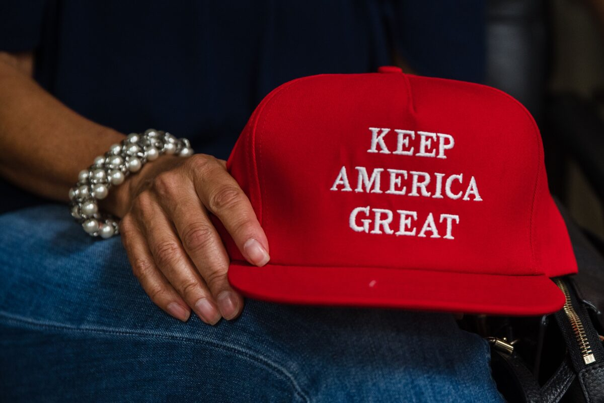 """Deborah Palomba holds a """"Keep America Great"""" hat as she watches US President Donald Trump acceptance speech for the Republican Party nomination for reelection during the final day of the Republican National Convention on TV in the office of San Diego County's Republican Party in Rancho Bernardo, California on August 27, 2020. - President Donald Trump tore into his election challenger Joe Biden as a threat to the """"American Dream"""" in a bruising speech August 27 accepting the Republican nomination for a second term against a backdrop of racial tensions and the deadly coronavirus pandemic. (Photo by ARIANA DREHSLER / AFP) (Photo by ARIANA DREHSLER/AFP via Getty Images)"""