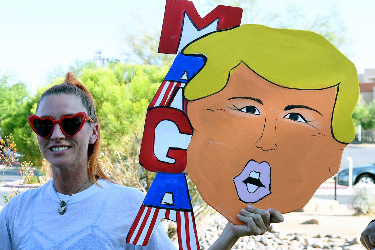 A Trump supporter holds a homemade MAGA sign shaped like Trump's head