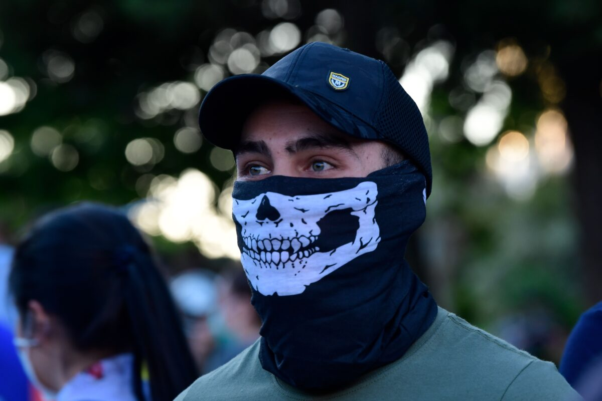 A demonstrator covers his face with a neck gaiter as he takes part in a demonstration against the government's handling of the coronavirus crisis, on May 20, 2020, in Alcorcon, near Madrid. - Spain's prime minister won parliamentary backing extend the lockdown for another two weeks today, despite opposition from his rightwing opponents and protests against his minority coalition government. It was the fifth time the state of emergency has been renewed, meaning the restrictions will remain in force until June 6 in a measure passed by 177 votes in favour, 162 against and 11 abstentions. (Photo by JAVIER SORIANO / AFP) (Photo by JAVIER SORIANO/AFP via Getty Images)