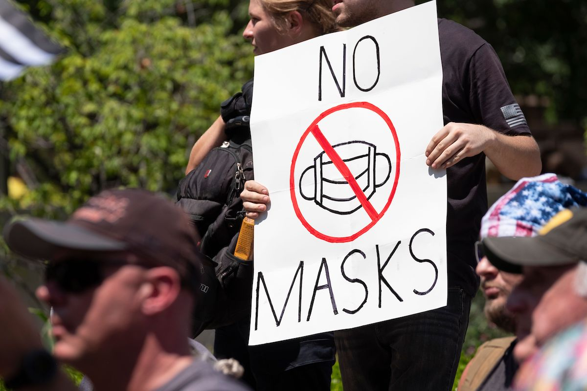 An anti-mask protestor holds up a sign in front of the Ohio Statehouse