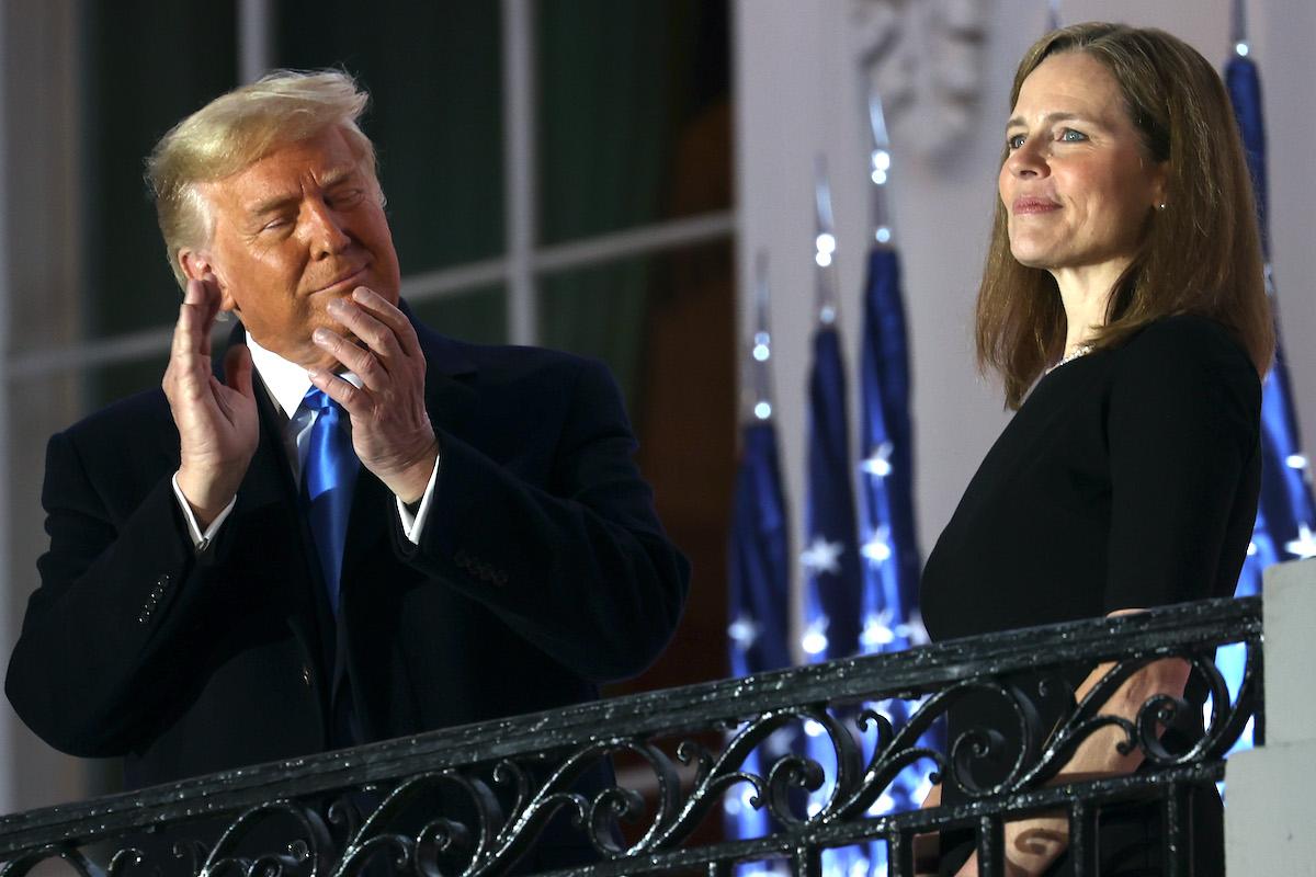 Donald Trump applauds Amy Coney Barrett on the White House balcony.