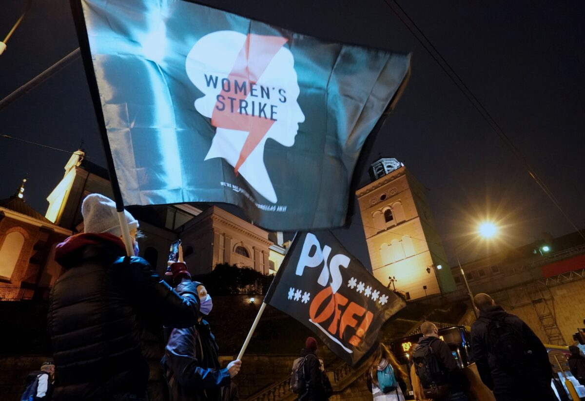 Demonstrators wave flags as they block a street during a protest against the tightening of Poland's already restrictive abortion law on November 2, 2020 in Warsaw. - Women in Poland hit the streets nationwide on November 2, the twelfth straight day of mass protests over a court ruling to impose a near-total abortion ban in Poland. (Photo by JANEK SKARZYNSKI / AFP) (Photo by JANEK SKARZYNSKI/AFP via Getty Images)