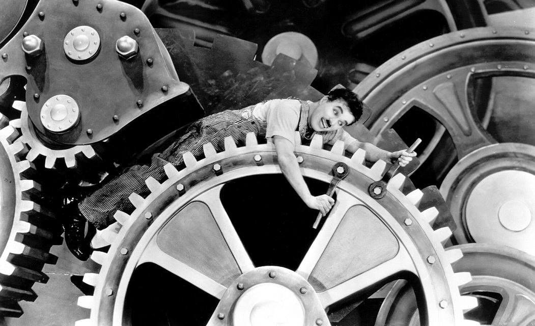 Charlie Chaplin as a factory worker caught in giant gears in Modern Times