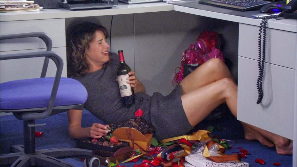 robin under a desk drinking wine and crying