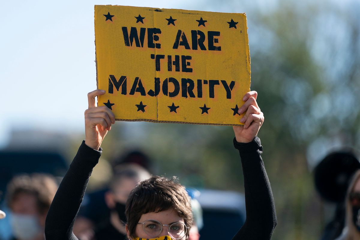 A protester holds a sign reading 'we are the majority.'