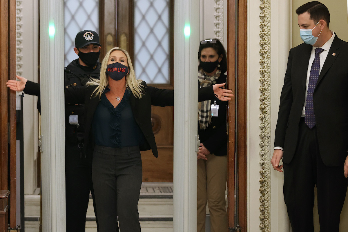"Rep. Marjorie Taylor Greene is searched by U.S. Capitol Police after setting off the metal detector. She is wearing a mask reading ""Molon Labe,"" meaning ""come and take them."""