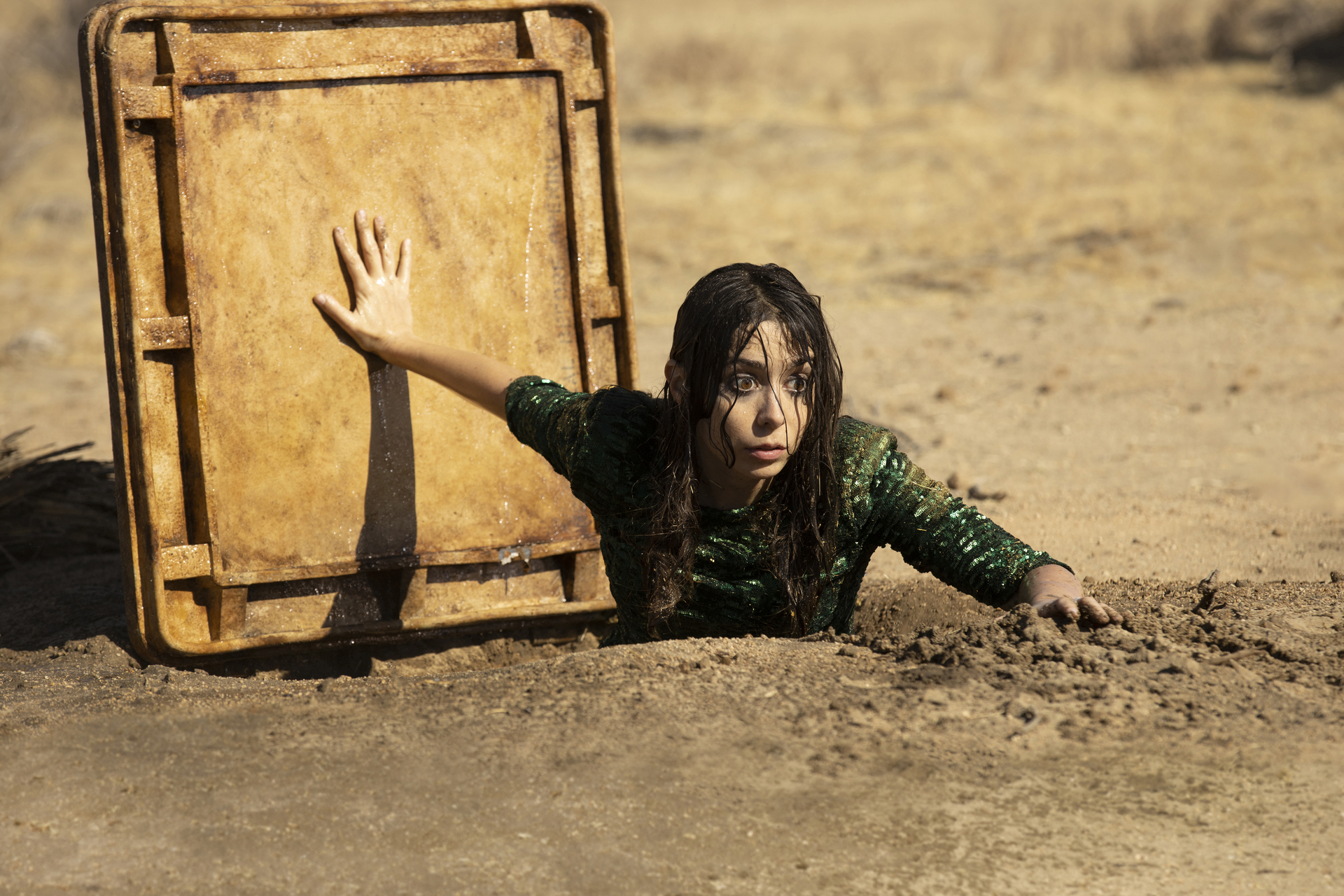 Cristin Milioti as Hazel in Made for Love, climbing out of the metal hatch to an underground waterway in the desert.