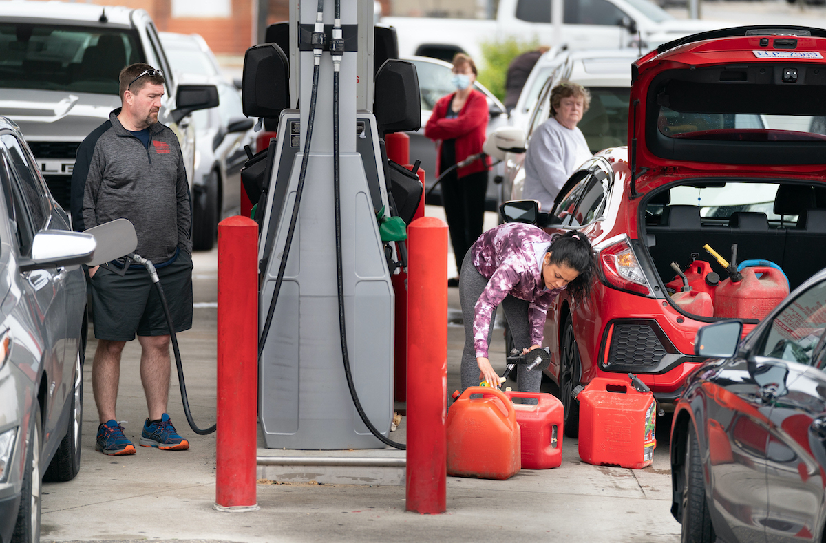 A woman fills her trunk with gas canisters while other motorists silently judge her.