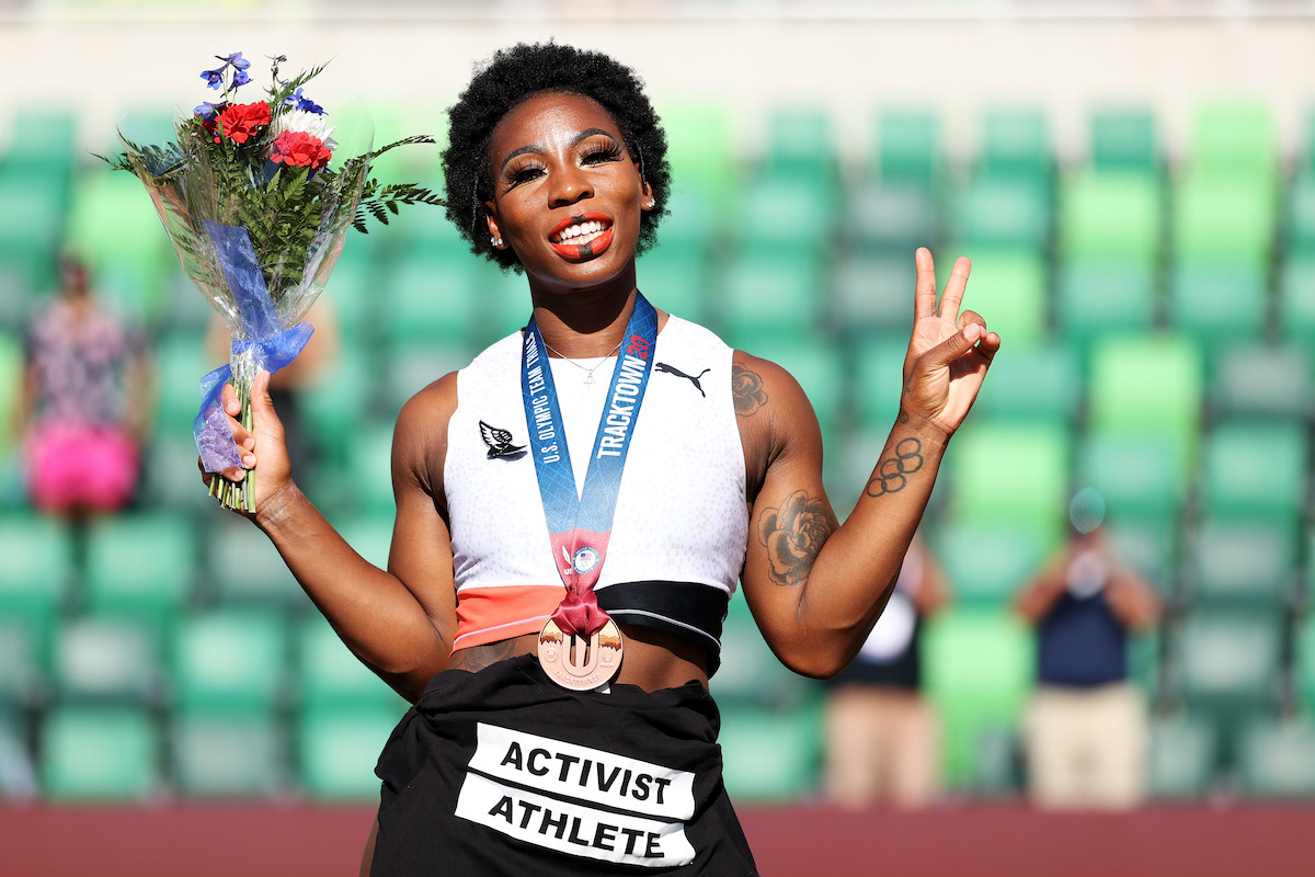 """Gwen Berry smiles holding a bouquet of flowers and flashes a peace sign, wearing a bronze medal around her neck and a shirt tied around her waist reading """"activist athlete"""""""
