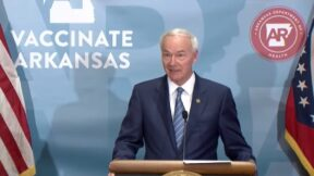 Arkansas Governor Asa Hutchinson speaks from a podium during a news conference